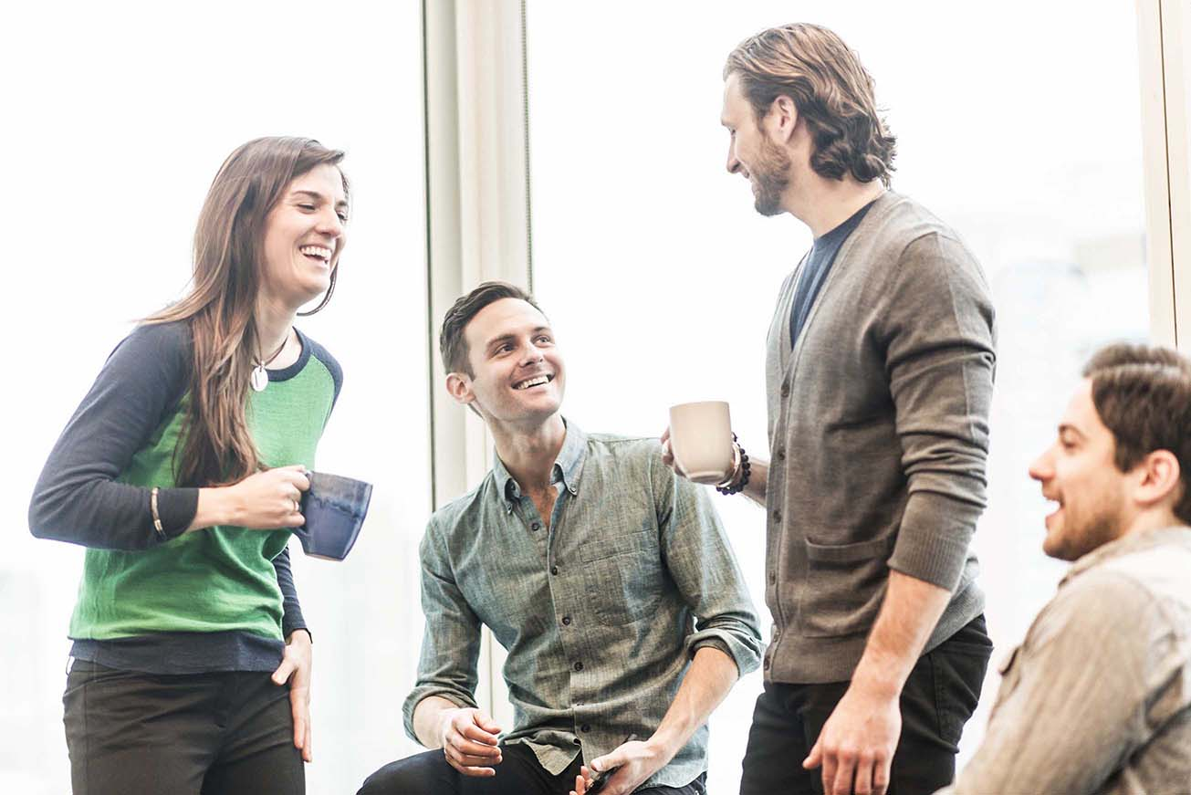 four-work-colleagues-on-a-break-laughing-together-TYSQT25